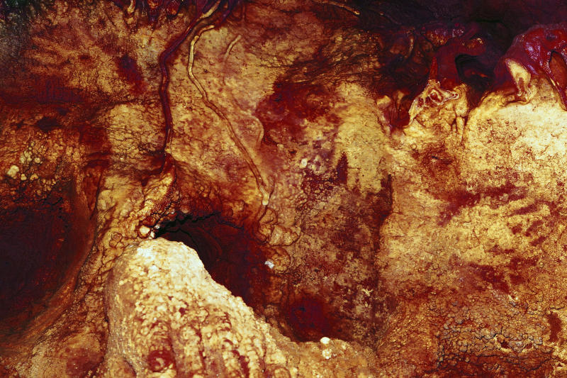This color enhanced image provided by Hipolito Collado Giraldo in February 2018 shows three hand stencils in the Maltravieso Cave in Cáceres, Spain. One has been dated to at least 66,000 years ago. New discoveries in some Spanish caves give the strongest evidence yet that Neanderthals created art. (Hipolito Collado Giraldo via AP)