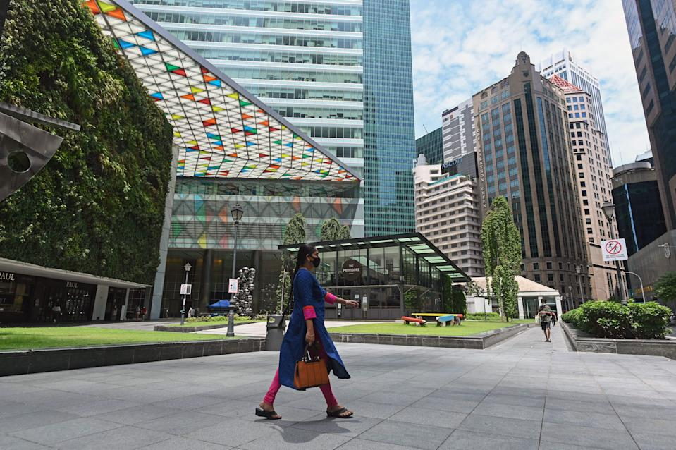 A woman wearing a facemask as preventive measure against the spread of the COVID-19 coronavirus walks at the Raffles Place central business district in Singapore on May 22, 2020. (Photo by ROSLAN RAHMAN / AFP) (Photo by ROSLAN RAHMAN/AFP via Getty Images)
