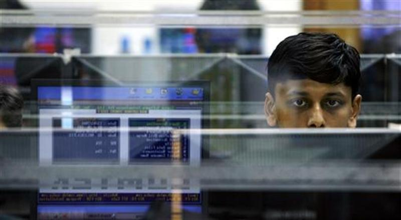A trader looks at a screen at a stock brokerage firm in Mumbai