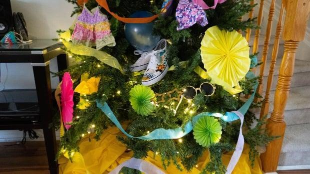 The Victoria Day long weekend tree is adorned with summer necessities like sunscreen, sneakers and sunglasses.