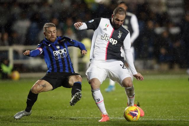 Juventus' Gonzalo Higuain is challenged by Atalanta's Papu Gomez, left, during the Serie A soccer match between Atalanta and Juventus at the Azzurri d'Italia Stadium in Bergamo, Italy, Italy, Saturday, Nov. 23, 2019. (AP Photo/Antonio Calanni)