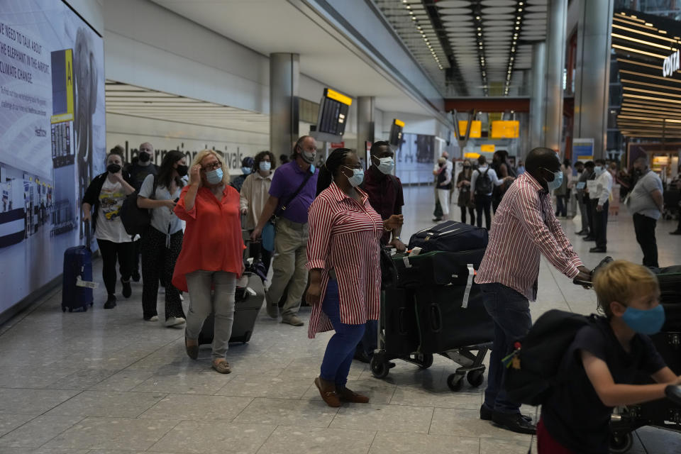 Passengers arrive at Terminal 5 of Heathrow Airport in London, Monday, Aug. 2, 2021. Travelers fully vaccinated against coronavirus from the United States and much of Europe were able to enter Britain without quarantining starting today, a move welcomed by Britain's ailing travel industry. (AP Photo/Matt Dunham)