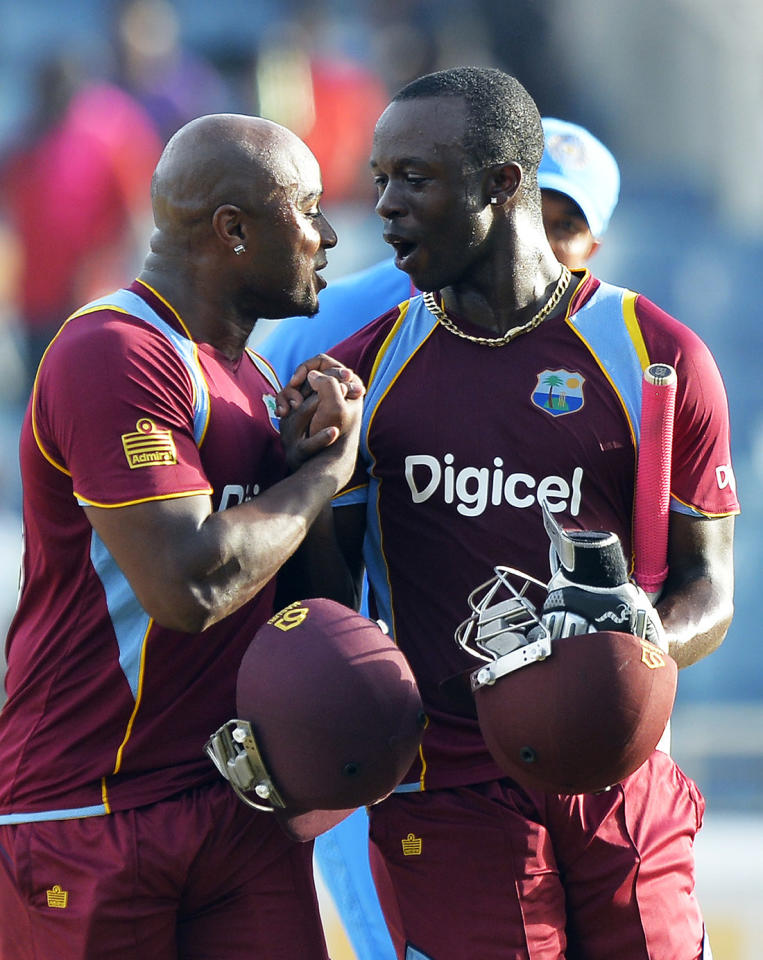 West Indies cricketers Kemar Roach (R) and Tino Best celebrate defeating India during the second match of the Tri-Nation series between Indian and West Indies at the Sabina Park stadium in Kingston on June 30, 2013. West Indies defeated India by 1 wicket. AFP PHOTO/Jewel Samad