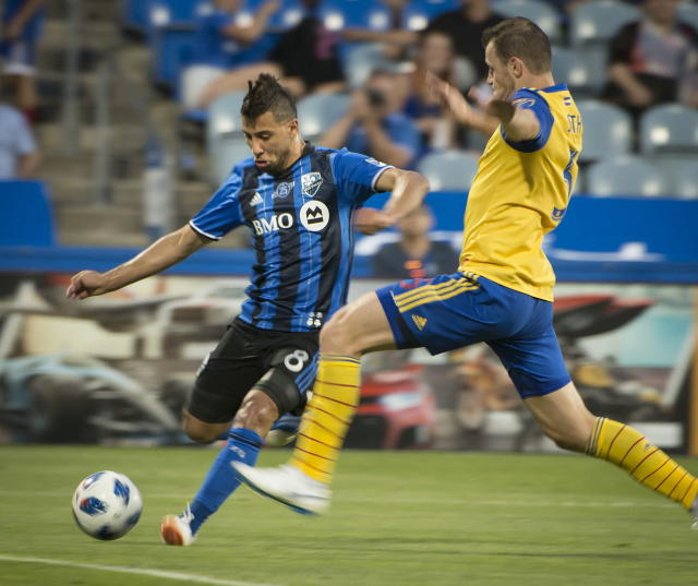 Montreal Impact's Saphir Taider takes a shot next to a Colorado Rapids player to score during the second half of an Major League Soccer match Saturday, July 7, 2018, in Montreal. (Peter McCabe/The Canadian Press via AP)