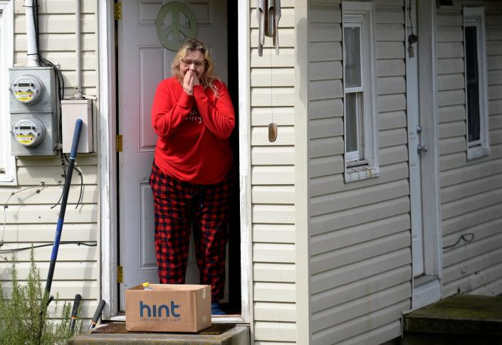 Jennifer Clinger reacts after receiving food and other supplies from Thistle Farms volunteer Levi Hummon on March 26 in Nashville, Tenn. Front Porch Delivery started for current and former Thistle Farm clients after the coronavirus started spreading in Nashville.