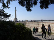 Tourists walk on Kalemegdan fortress in Belgrade, Serbia, Sunday, Oct. 3, 2021. Russians are flocking to Serbia to receive Western-approved COVID-19 shots. Although Russia has its own vaccine known as Sputnik V, the shot has not been approved by international health authorities. (AP Photo/Darko Vojinovic)