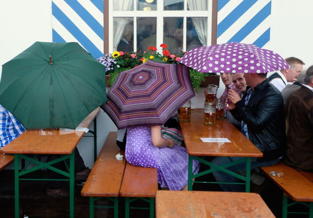 Warm days, cold beer. Protected with umbrellas revellers drink beer outside Schottenhamel beer tent at the world's biggest beer festival, Oktoberfest.