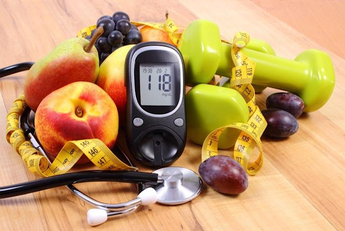 Glucose meter with medical stethoscope, fruits and dumbbells for using in fitness, concept of diabetes, healthy lifestyles and nutrition
