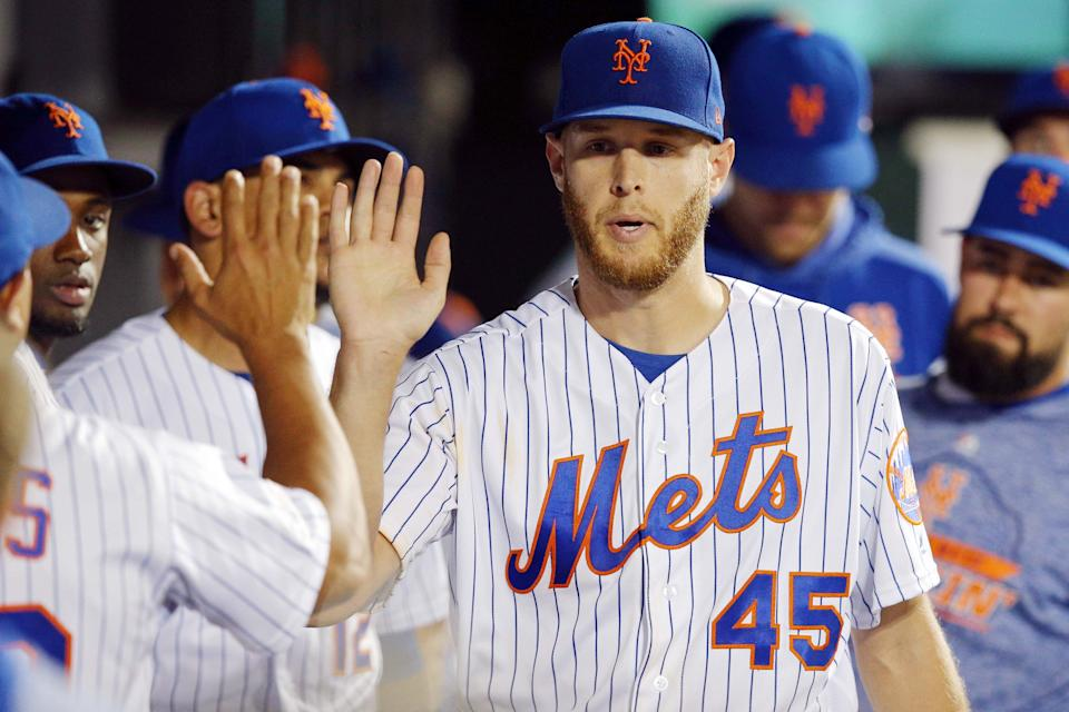 Jul 2, 2019; New York City, NY, USA; New York Mets starting pitcher Zack Wheeler (45) is greeted in the dugout by teammates after coming out of the game against the New York Yankees during the seventh inning at Citi Field. Mandatory Credit: Brad Penner-USA TODAY Sports