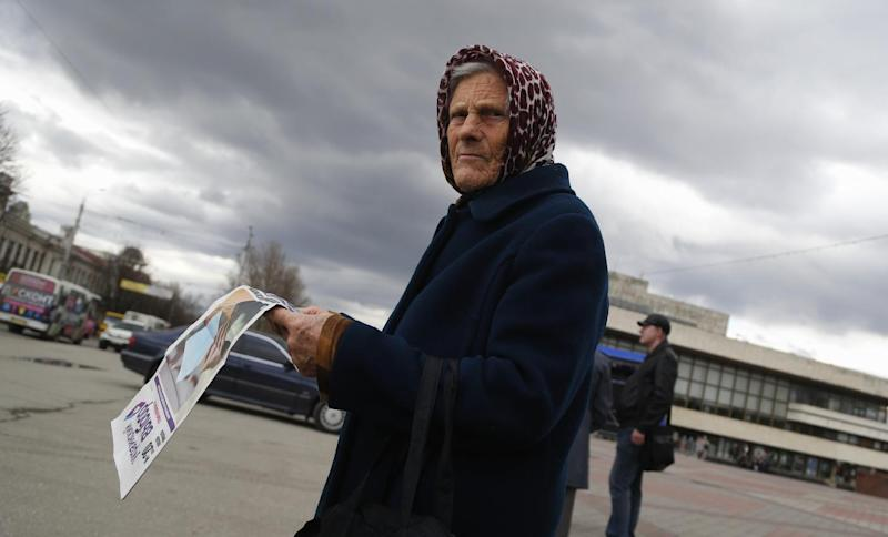 "In this photo taken Wednesday, March 5, 2014, an elderly woman reads newspaper named ""Ukrainian choice"" at a central square in Simferopol, Ukraine. Ukraine is facing a potentially crippling geographic and cultural divide, a growing gulf between supporters of Russia who dominate the east and south of the country, and western Ukrainians who yearn for closer ties to Western Europe. One side of that divide is even starker in Crimea, a Black Sea peninsula. For much of the past 200 years, Crimea was under Russian and Soviet control, and today most Crimeans see themselves as only nominally Ukrainian and Russian is, by far, the dominant language (AP Photo/Sergei Grits)"