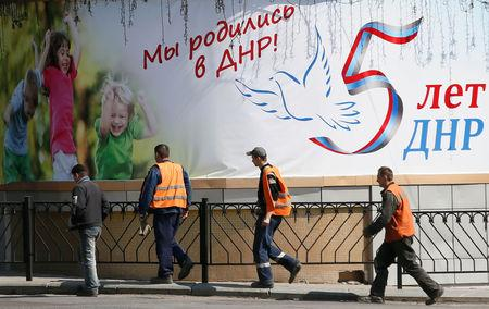 "Men walk past a banner, which reads ""We were born in DPR (Donetsk People's Republic)! DPR is five years old"", in a street in the separatist-controlled city of Donetsk, Ukraine April 25, 2019. REUTERS/Alexander Ermochenko"