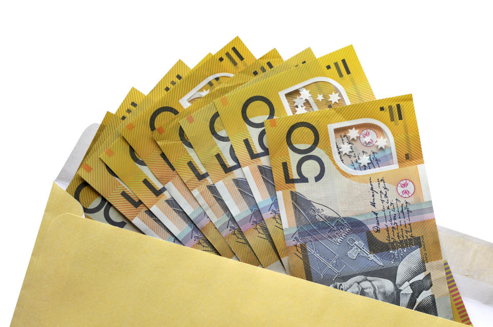 Australian $50 dollar notes coming out of an envelope isolated on white background