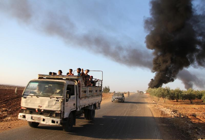 Syrians fleeing from the town of Souran, in northern Hama, drive past burning vehicles on September 1, 2016