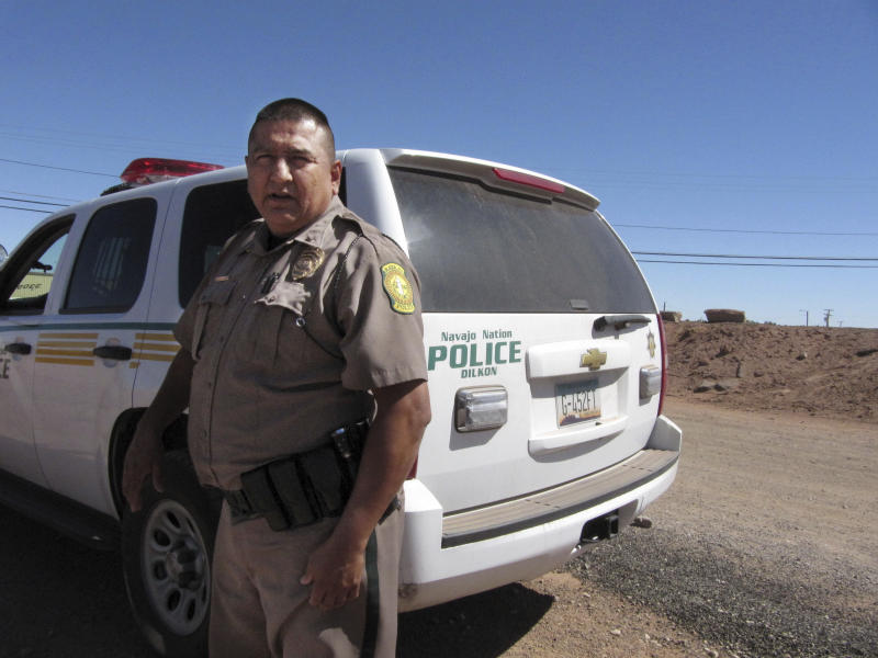 FILE - In this Sept. 23, 2009 file photo, Navajo Nation police Lt. Clifton Smith stands nearby the future site of a proposed tribal jail on the reservation in Tuba City, Ariz. The tribe is one of 10 that is getting access to national anti-crime databases under an expansion of an Obama administration program by U.S. Attorney General Jeff Sessions. (AP Photo/Felicia Fonseca, File)