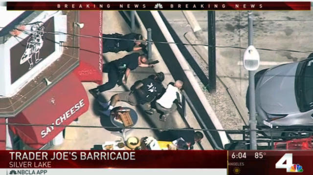 <p>Police and civilians take cover near a Trader Joe's supermarket where a hostage situation was underway in the Silverlake district of Los Angeles on Saturday. (Photo: KNBC-TV via AP) </p>