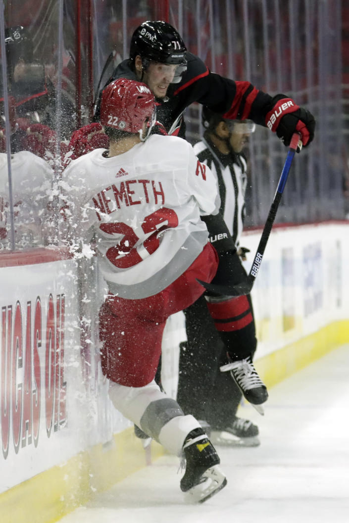 Detroit Red Wings' Patrik Nemeth (22) is checked by Carolina Hurricanes' Jesper Fast (71) during the second period of an NHL hockey game in Raleigh, N.C., Thursday, March 4, 2021. (AP Photo/Chris Seward)