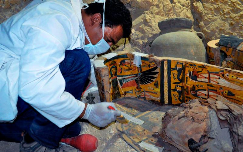 An archaeologist works on a wooden coffin discovered in a 3,500-year-old tomb in the Draa Abul Nagaa necropolis, near the southern Egyptian city of Luxor, on April 18, 2017 - Credit: AFP