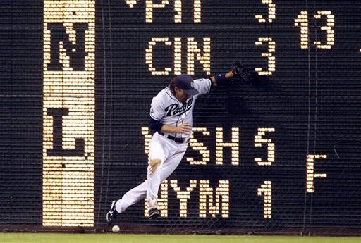 San Diego Padres right fielder Chris Denorfia (13) misses the ball against the fence, as St. Louis Cardinals' Matt Holliday hits a double during the sixth inning of their baseball game in San Diego, Monday, Sept. 10, 2012. (AP Photo/Alex Gallardo)