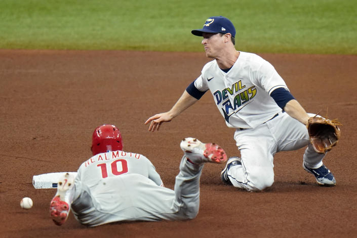 Philadelphia Phillies' J.T. Realmuto (10) gets hit with the ball as he steals second base while Tampa Bay Rays shortstop Joey Wendle waits for the throw during the fourth inning of a baseball game Saturday, May 29, 2021, in St. Petersburg, Fla. (AP Photo/Chris O'Meara)