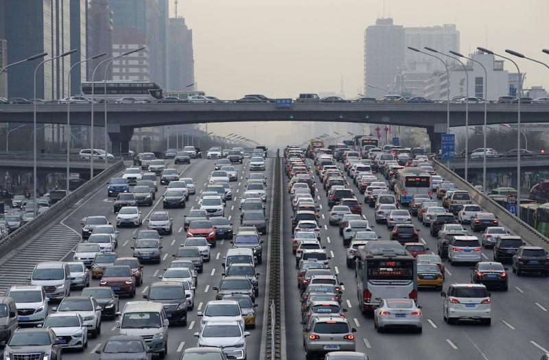 FILE PHOTO: Cars drive on a main road through Beijing's central business area
