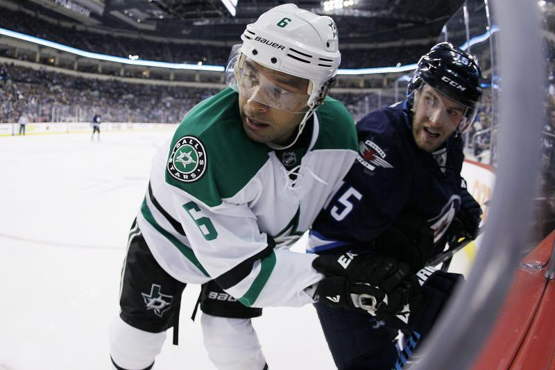 Dallas Stars' Trevor Daley (6) and Winnipeg Jets' Matt Halishchuk (15) fight for position in the Stars' corner during second-period NHL hockey game action in Winnipeg, Manitoba, Friday, Oct. 11, 2013. (AP Photo/The Canadian Press, John Woods)