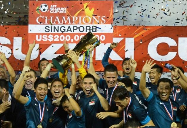 Singapore football players celebrate with the trophy after defeating Thailand during their AFF Suzuki football Cup final second leg in Bangkok last year. Singapore beat Thailand 3-2. (AFP PHOTO / PORNCHAI KITTIWONGSAKU)