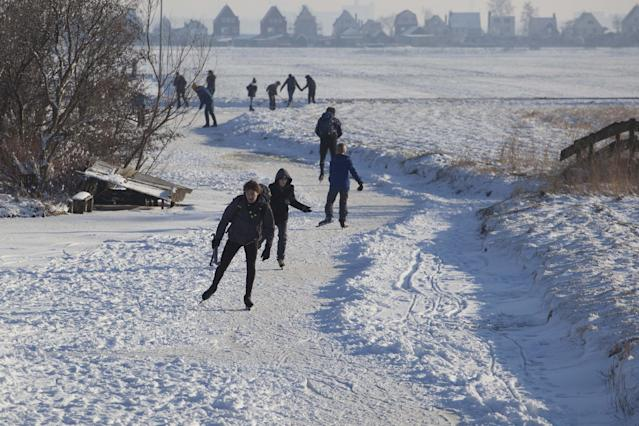 FILE - In this Feb. 4, 2012, file photo, skaters enjoy the sun and frozen canals in the village of Ransdorp, north of Amsterdam. There is nothing more mythical in Dutch sports than an age-old 11-city race skating across lakes and canals in bone-numbing cold from dawn to dusk. No wonder the Netherlands is the greatest speedskating nation in the world. And with Sven Kramer and Ireen Wust leading the way on big oval in Sochi they are bent on proving it again. (AP Photo/Peter Dejong, File)