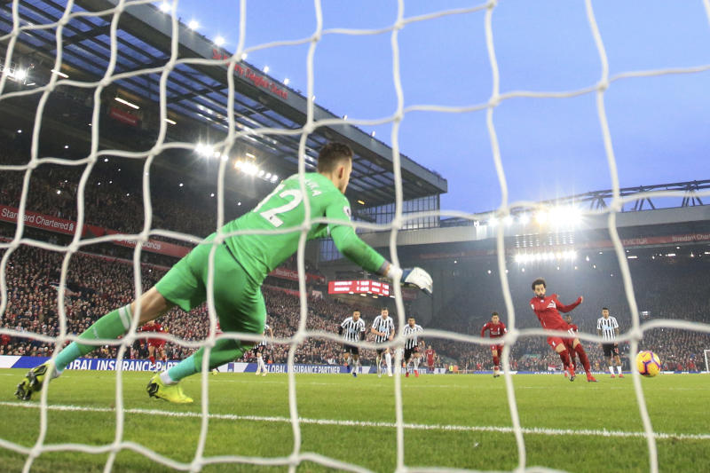Liverpool'sMohamed Salah, right, scores on a penalty kick during the English Premier League soccer match between Liverpool and Newcastle at Anfield Stadium, Liverpool, England, Wednesday, Dec. 26, 2018. (AP Photo/Jon Super)