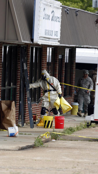 Federal authorities, some in hazmat suits, walk outside the staging area as they search the site of a martial arts studio once operated by 41-year-old Everett Dutschke, Wednesday, April 24, 2013 in Tupelo, Miss., in connection with the investigation into poisoned letters mailed to President Barack Obama and others. (AP Photo/Rogelio V. Solis)