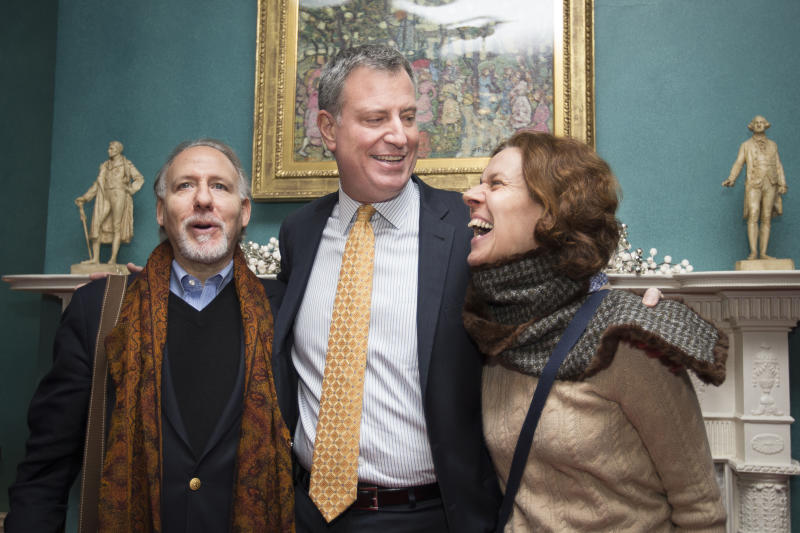 """FILE - In this Jan. 5, 2014 file photo, New York City Mayor Bill de Blasio smiles while posing for pictures with visitors at Gracie Mansion in New York, during an open house and photo opportunity with the public. The newly elected de Blasio stooped his 6-foot-5 frame for hours to shake hands with regular New Yorkers touring Gracie Mansion, telling them the opulent mayoral residence was """"the people's house."""" De Blasio's first few weeks in office have offered a look at a mayor skilled in the art of political stagecraft: with the goal, in his case, of coming across as a regular Joe. (AP Photo/John Minchillo, File)"""