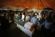 People attend the funeral prayer for Pakistani nuclear scientist Abdul Qadeer Khan, in Islamabad, Pakistan, Sunday, Oct. 10, 2021. Khan, a controversial figure known as the father of Pakistan's nuclear bomb, died Sunday of COVID-19 following a lengthy illness, his family said. He was 85. (AP Photo/Anjum Naveed)