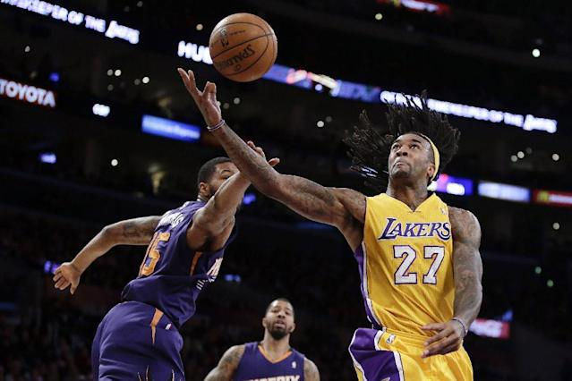 Los Angeles Lakers center Jordan Hill, right, is fouled by Phoenix Suns forward Marcus Morris during the first half of an NBA basketball game in Los Angeles, Tuesday, Dec. 10, 2013. (AP Photo/Chris Carlson)
