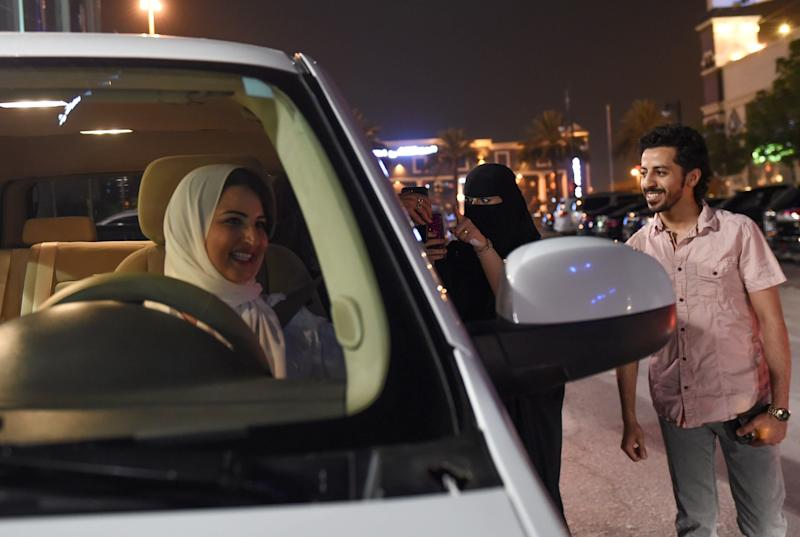 A Saudi woman films and shows support to Samar Almogren (left), who drives her car through the streets of the Saudi capital Riyadh for the first time just after midnight, June 24, 2018, when the law allowing women to drive took effect. (FAYEZ NURELDINE via Getty Images)