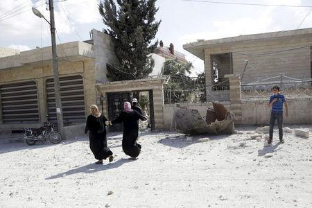 Women run at a site hit by what activists said were airstrikes carried out by the Russian air force in Kafranbel, near Idlib Syria October 10, 2015. REUTERS/Khalil Ashawi