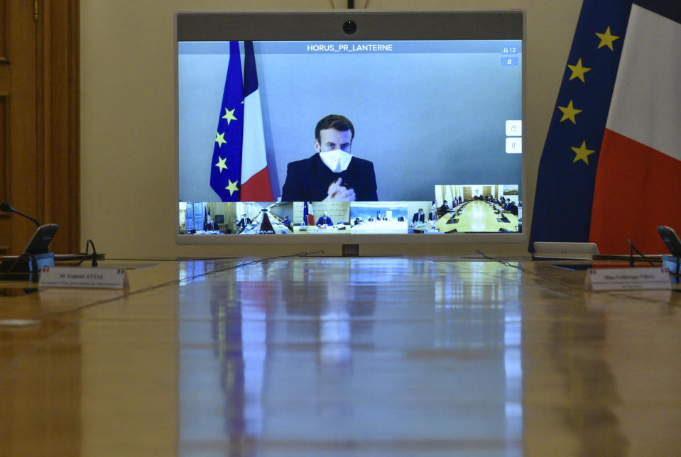 """French President Emmanuel Macron is seen on a screen from his presidential residence in Versailles as he attends by video conference the weekly cabinet meeting at the Elysee Palace in Paris, Monday, Dec. 21, 2020. French President Emmanuel Macron held a cabinet meeting Monday via video, in which he indicated the French could enforce """"systematic tests"""" as a condition for French nationals returning from Britain to France for the holidays. (Julien de Rosa/Pool Photo via AP)"""