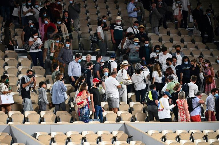 Closing time: Spectators leave Court Philippe Chatrier due to the 11pm curfew