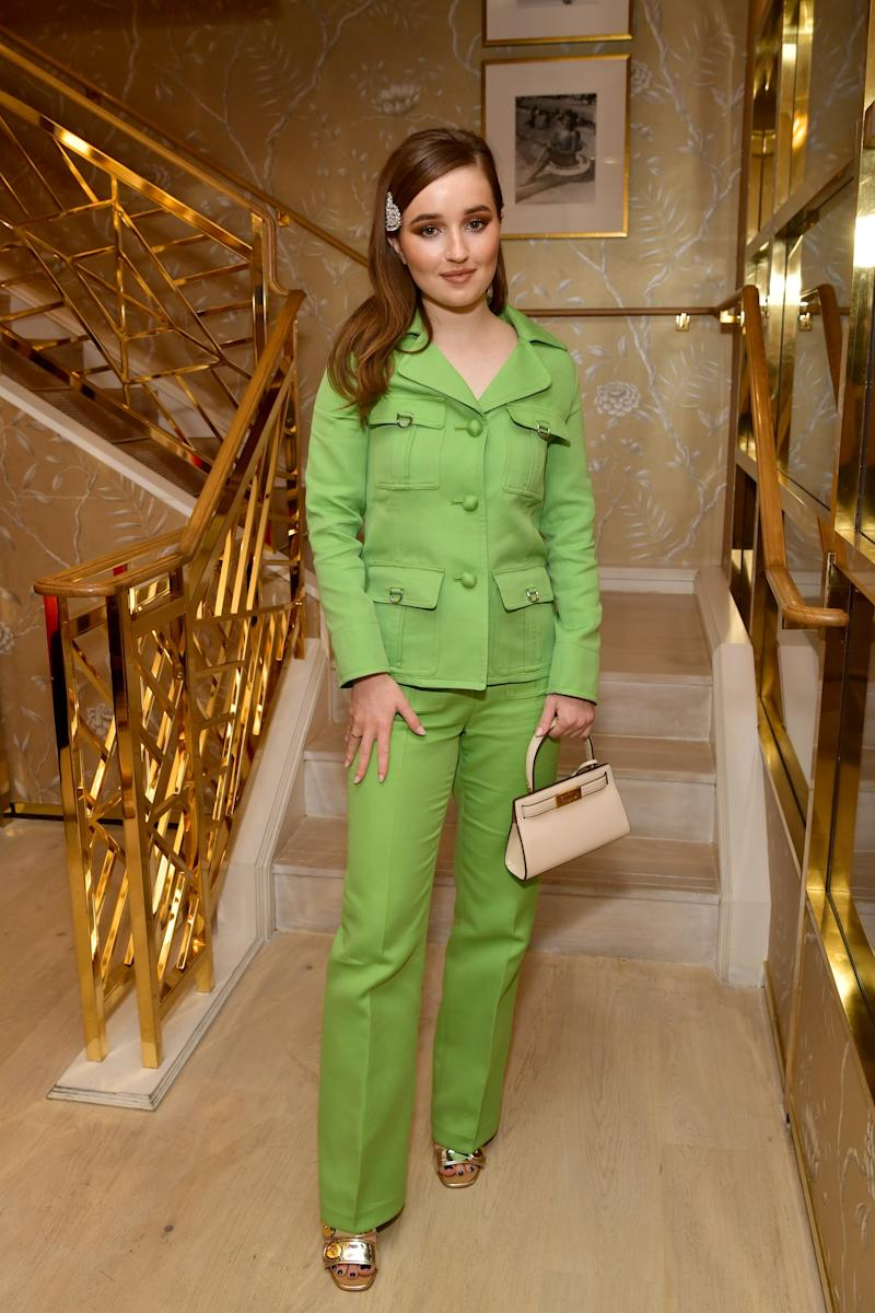 Kaitlyn Dever is wearing the Twill Sgt. Pepper Jacket, D-Ring Pant, Madison Triple-Band Mule, Lee Radziwill Petite Bag, and Raffia Square Sunglasses.