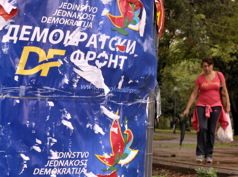 "A woman passes by main opposition Democratic Front election poster reading ""Unity, Equality, Democracy - Democratic Front"",  in downtown Podgorica, Montenegro, Friday, Oct. 12, 2012, two days ahead of parliamentary elections scheduled for upcoming October 14. Montenegro's ruling coalition of longtime leader Milo Djukanovic is again a favorite to win weekend parliamentary elections in the tiny Balkan nation seeking membership in the European Union. (AP Photo/Risto Bozovic)"