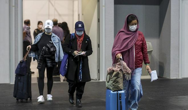 Arrivals into Hong Kong leave a testing facility near the airport at AsiaWorld-Expo as the government ramps up anti-contagion measures on another record day in the city for new infections. Photo: Winson Wong