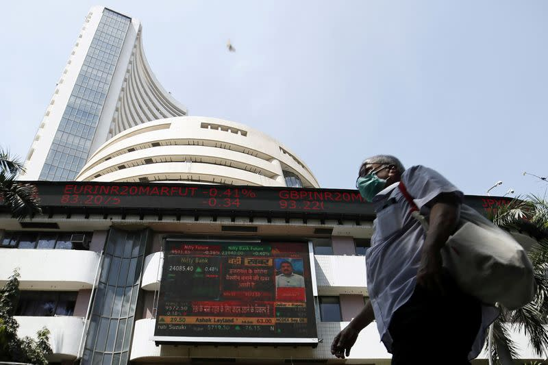 FILE PHOTO: A man wearing a protective mask walks past the Bombay Stock Exchange (BSE) building in Mumbai