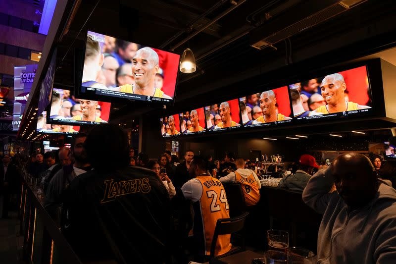 Fans of NBA basketball star Kobe Bryant watch a replay of his last NBA game as they sit at an outdoor bar near the Staples Center at L.A. Live in Los Angeles,