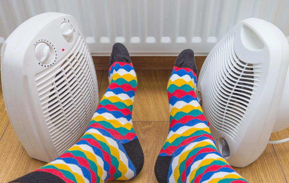 Feet in bright multicolored socks near heaters at home. Symbolic image of home heating in the cold winter season. Close-up, selective focus.