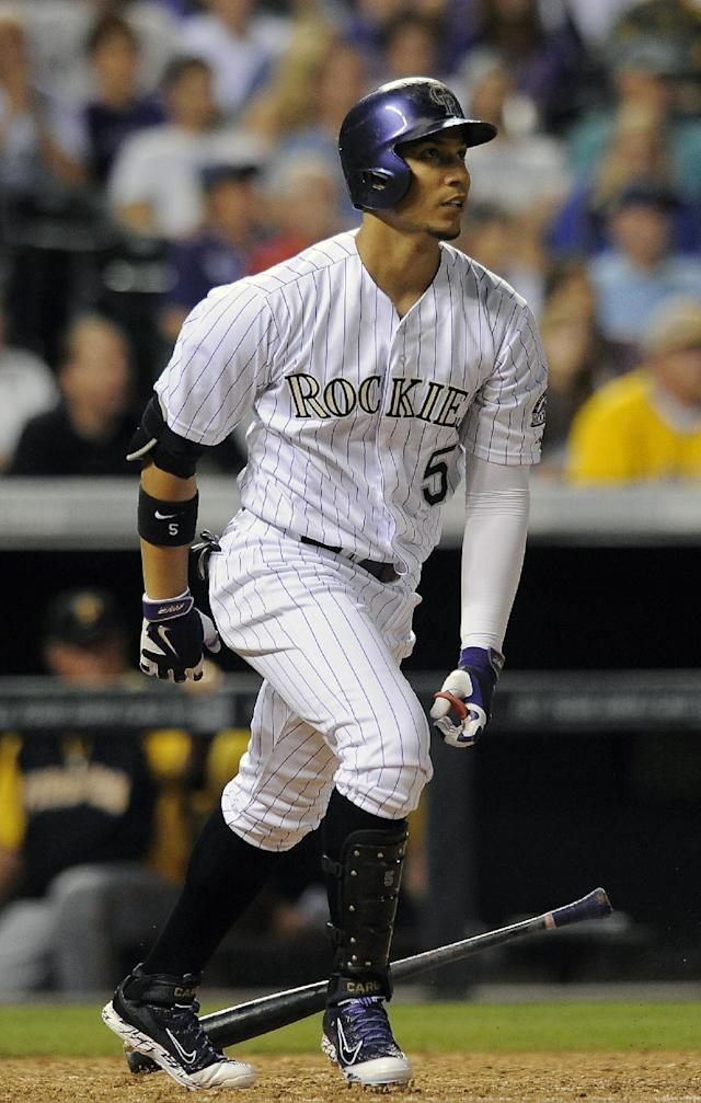 Colorado Rockies' Carlos Gonzalez watches his home run sail over the wall in the seventh inning of a baseball game against the Pittsburgh Pirates on Friday, July 25, 2014, in Denver. (AP Photo/Chris Schneider)