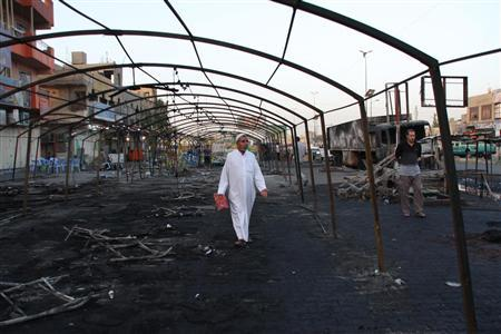 A man walks through the remains of a tent that was hit by a triple bomb attack in Baghdad's Sadr City