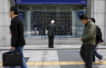 Man looks at a stock quotation board outside a brokerage in Tokyo