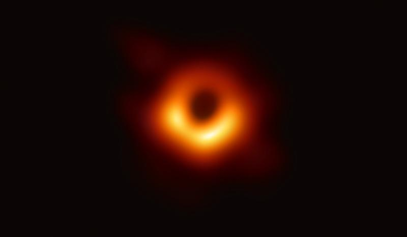 the first ever direct image of a black hole, with yellow ring surrounding black circle