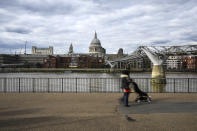 People walk on the south bank of River Thames, against the backdrop of St Paul's Cathedral, in London, Monday, Aug. 31, 2020. Today is the last day of the 'Eat out to help out' scheme, the UK Government's initiative to support restaurants, cafés, bars and pubs. (AP Photo/Alberto Pezzali)