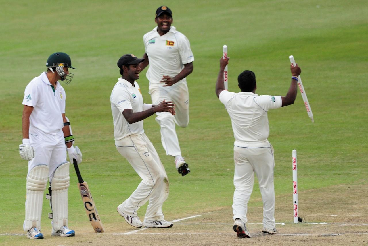 South Africa's Imran Tahir, left, looks on as Sri Lanka's Rangana Herath celebrates winning their first test match during their second five-day cricket test match in Durban, South Africa, Thursday, Dec. 29, 2011. (AP Photo)