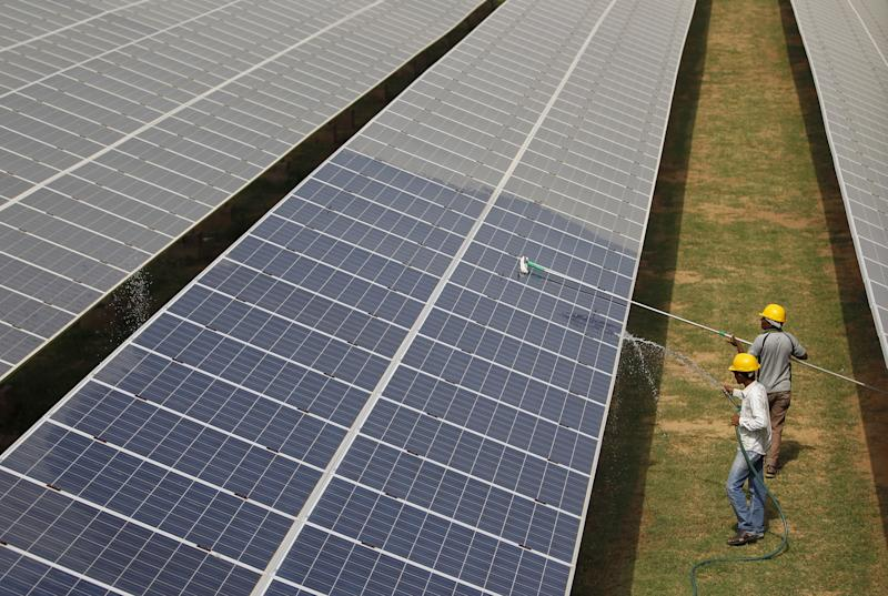 Workers clean photovoltaic panels inside a solar power plant in Gujarat.