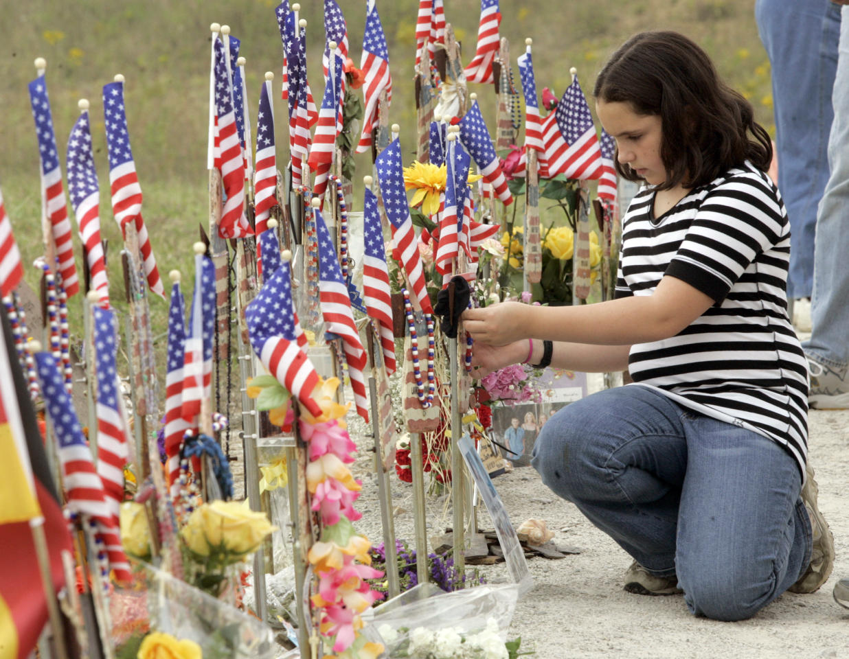 Jody Greene, 11, of Greenwhich, Connecticut, adjusts a ribbon on a memorial for her father Donald Greene at the Flight 93 Temporary Memorial just outside Shanksville, Pennsylvania, September 10, 2006. Jody's father was one of the 40 people who died on board Flight 93. (REUTERS/Jason Cohn)